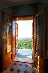 Spectacular mountain view from balcony window through opened wooden shutters