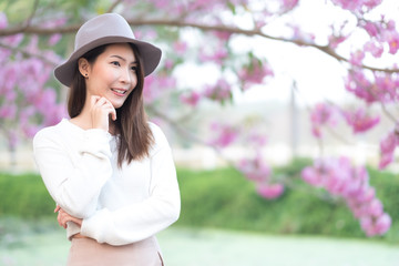 Young woman with smiling under cherry blossom in garden. Springtime