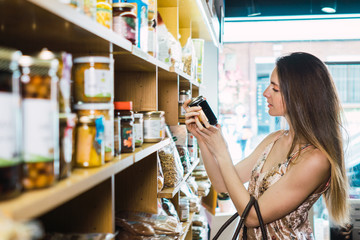 Attractive female picking up jam jar in store