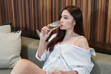 woman drinking water on sofa in living room