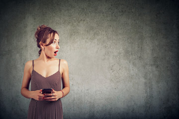 Portrait of a surprised woman holding mobile phone and looking away at copy space