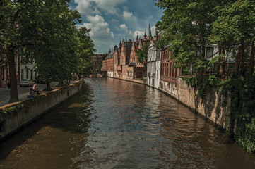 Wooded gardens and brick buildings on the canal's edge in a sunny day at Bruges. With many canals and old buildings, this graceful town is a World Heritage Site of Unesco. Northwestern Belgium.