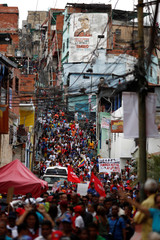 Supporters of Venezuela's President Nicolas Maduro walk past a mural depicting late President Hugo Chavez, during a campaign rally in Caracas