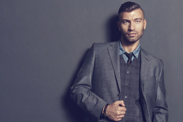 Male fashion model in elegant suit on gray wall background. Handsome man in fashionable clothes. Portrait of young brunette businessman.