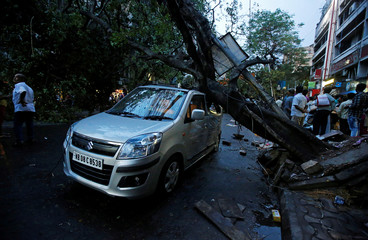 People stand beside a damaged car by a fallen tree after heavy rain and storm in Kolkata