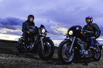 Modern bikers sits and talks on classic motorcycle at sunset. Outdoor portrait and urban lifestyle