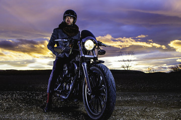 Modern biker sits and watches landscape on classic motorcycle at sunset. Outdoor portrait and urban lifestyle