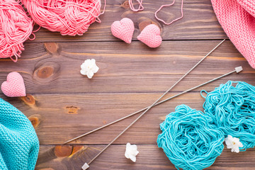 Tangles of pink and mint yarn, snuds, needles and knitting hearts on a wooden background. Top view