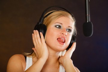 Woman singing to microphone wearing headphones in studio