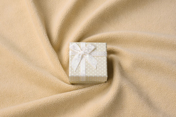 A small gift box in orange with a small bow lies on a blanket of soft and furry light orange fleece fabric with a lot of relief folds. Packing for a gift to your lovely girlfriend