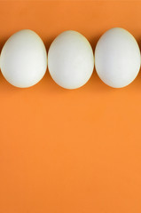 A few white easter eggs on a bright orange background