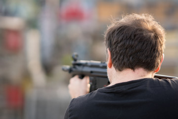 Back turned caucasian man taking aim at the target with a sniper rifle