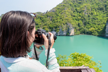 Woman tourist on Koh Mae Ko island viewpoint use camera taking photos at beautiful nature landscape of Thale Nai or Blue Lagoon (Emerald Lake) in Mu Ko Ang Thong National Park, Surat Thani, Thailand