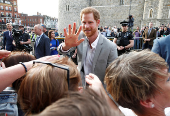 Britain's Prince Harry greets wellwishers outside Windsor Castle ahead of his wedding to Meghan Markle tomorrow, in Windsor