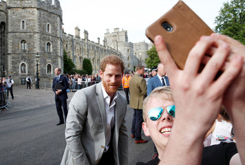 Britain's Princes Harry and William greet wellwishers outside Windsor Castle ahead of Harry's wedding to Meghan Markle tomorrow, in Windsor