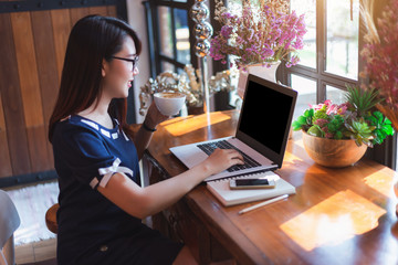 Asian business female working with laptop make a note in coffee shop like the background.
