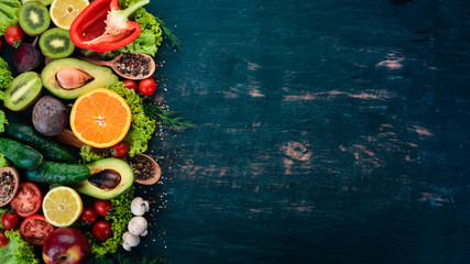 Healthy food. Vegetables and fruits On a black wooden background. Top view. Copy space.