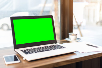 Green screen of Mockup image of laptop with blank screen on wooden table.