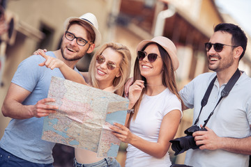 Group of smiling friends with map