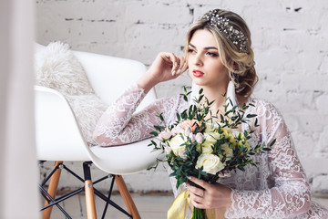 beautiful girl dressed in peignoir and underwear sits on floor and holds bouquet in her hands.