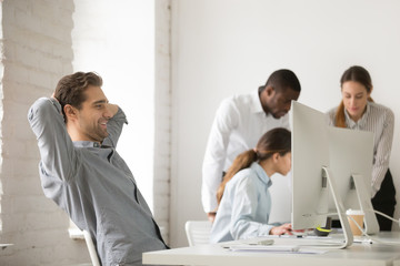 Happy businessman holding hands behind head resting after finishing work on computer in multiracial office, company manager employee taking break for relaxing at workplace satisfied with good result