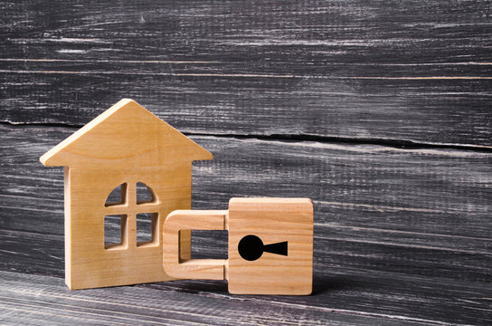 Wooden house with a padlock. House with a lock. Security and safety, collateral, loan for a mortgage. Confiscation of property for debts. Safety and alarm system. Buying a new home.