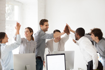 Excited multiracial colleagues celebrating team victory giving high five in office, happy employees group join hands together promising loyalty engagement, expressing trust unity support in teamwork