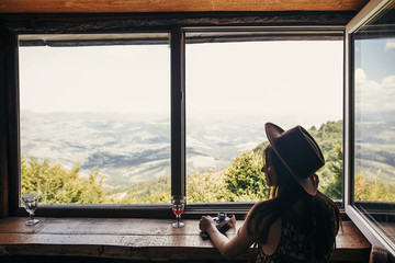 stylish girl traveler ih hat sitting at window with view on mountains and sky. happy hipster woman with camera relaxing. summer vacation concept. travel and wanderlust. space for text
