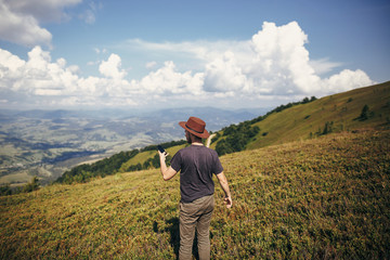 stylish traveler man in hat holding phone, walking on top of sunny mountains and sky. travel and wanderlust concept. space for text. happy hipster traveling and taking photo.