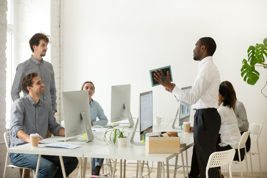 New african employee unpacking boxes and talking to friendly colleagues on first working day in office, smiling happy black worker having pleasant conversation with coworkers showing photo in frame
