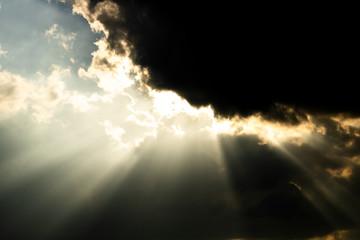 Sun shining through dark clouds