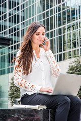 Way to Success. Young Eastern European Businesswoman traveling, working in New York, wearing white shirt, sitting outside of modern office building, working on laptop computer, talking on cell phone..