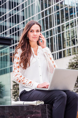 Way to Success. Young Eastern European Businesswoman traveling, working in New York, sitting outside of modern office building, working on laptop computer, talking on cell phone, looking, thinking..