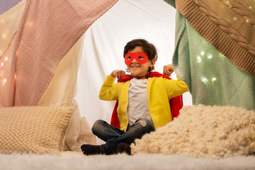 childhood and hygge concept - happy little boy wearing superhero mask and cape in kids tent or teepee at home