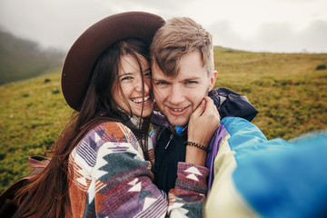 happy hipster couple making selfie on top of sunny mountains.  family hugging and smiling. summer vacation. space for text. atmospheric moment. travel and wanderlust concept