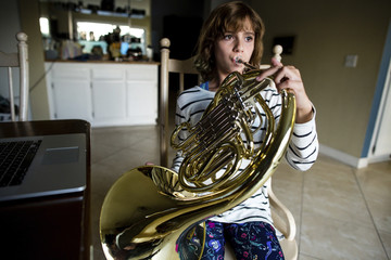 Girl playing French horn while sitting on chair at home