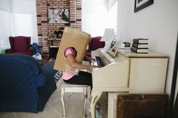 Side view of girl in cardboard box playing piano while sitting at home