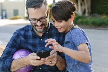 Father with son using mobile phone at park