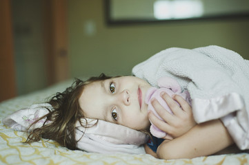 Portrait of girl with stuffed toy lying on bed at home