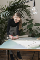 Businesswoman drawing blueprints while standing in office
