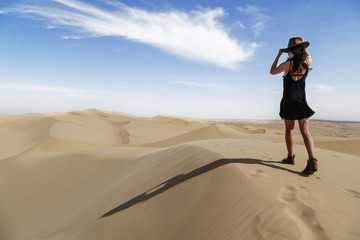 Rear view of young woman wearing hat while walking on sand dune at desert against sky during sunny day