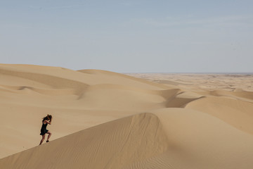 Side view of young woman wearing hat while climbing on sand dune at desert against sky