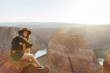 Full length portrait of young woman sitting on rock by Horseshoe Bend at desert during sunny day