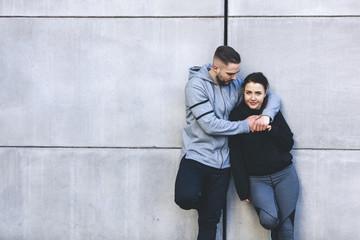 Portrait of girlfriend standing with boyfriend by wall in city