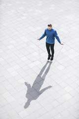 High angle view of man skipping on sidewalk in city