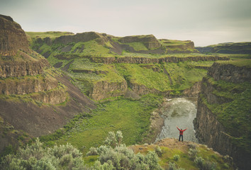 Rear view of man with arms outstretched standing at Palouse Falls State Park