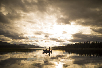 Distant view of father and son in boat on lake against cloudy sky during sunset