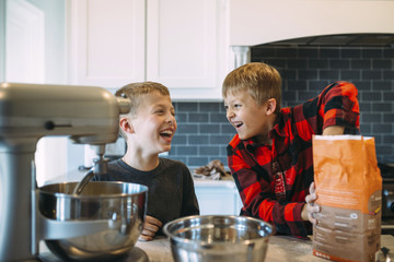 Happy brothers preparing food in kitchen at home