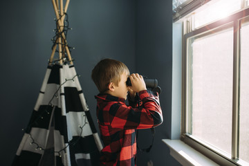 Side view of boy looking through binoculars by window at home