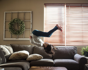 Full length of girl backflipping on couch at home
